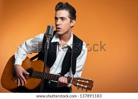 Retro country singer with guitar wearing black suit. Studio shot. - stock photo