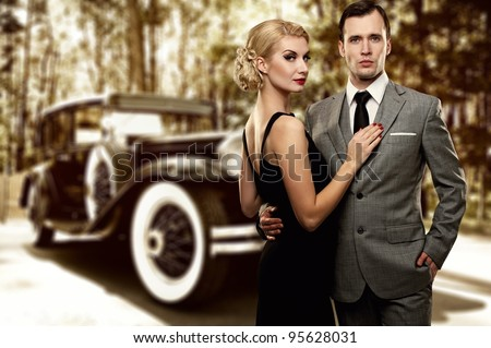 Retro couple against old car. - stock photo