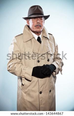 Retro detective man with mustache and hat. Wearing raincoat. Studio shot. - stock photo