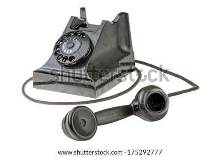Retro dial-up rotary telephone with the handset lying in the foreground turned towards the camera on a white studio background - stock photo