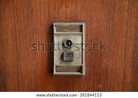 Retro doorbell with peephole on wooden door - stock photo