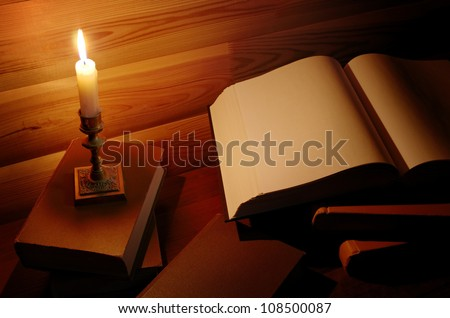 retro educational and reading still life: candle near an open book - stock photo