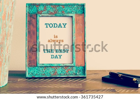 Retro effect and toned image of a vintage photo frame next to fountain pen and notebook . Motivational quote written with typewriter font TODAY IS ALWAYS THE BEST DAY - stock photo