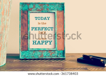 Retro effect and toned image of a vintage photo frame next to fountain pen and notebook . Motivational quote written with typewriter font TODAY IS THE PERFECT DAY TO BE HAPPY - stock photo