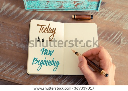 Retro effect and toned image of a woman hand writing a note with a fountain pen on a notebook. Handwritten text TODAY IS A NEW BEGINNING, motivation concept - stock photo