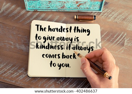Retro effect and toned image of a woman hand writing on a notebook. Handwritten quote The hardest thing to give away is kindness; it always comes back to you.  as inspirational concept image - stock photo