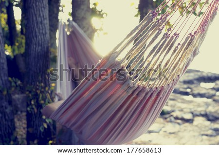 Retro effect faded and toned image of a person relaxing in a hammock in the shade of a tree on a shoreline viewed from behind. - stock photo