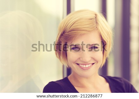 Retro effect portrait of a smiling young woman with short blond hair standing alongside an angled wall with copyspace - stock photo