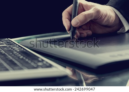 Retro effect toned image of a graphic designer working with digital tablet pen. - stock photo