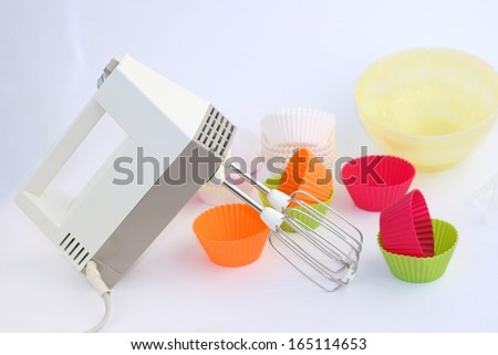 Retro electric hand mixer (eggbeater) with two beaters, Variety of cupcake liners and bowl in different colors in background - stock photo