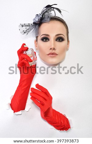 Retro fashion portrait of young woman with red gloves and bottle of perfume. - stock photo