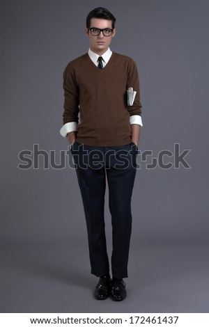 Retro fifties fashion man with dark grease hair. Wearing brown sweater with black tie and glasses. Holding newspaper. Studio shot against grey. - stock photo