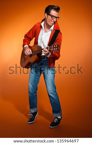 Retro fifties musician with glasses playing acoustic guitar. Studio shot. - stock photo