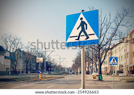Retro filtered photo of pedestrian crossing signs. - stock photo