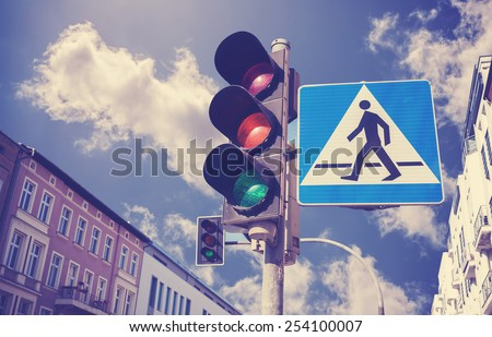 Retro filtered photo of traffic lights and pedestrian crossing sign in a city. - stock photo