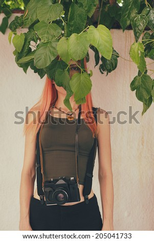 retro filtered photograph of a hipster girl hiding her face behind the leaves - stock photo