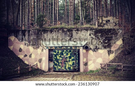 Retro filtered picture of a bunker in forest. - stock photo