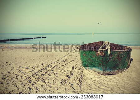 Retro filtered picture of an old rusty steel boat on the beach. - stock photo