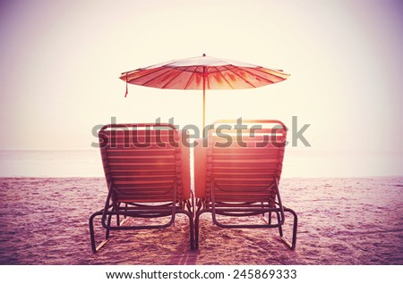 Retro filtered picture of beach chairs and umbrella on sand at sunset. Concept for rest, relaxation, holidays.  - stock photo
