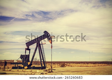 Retro filtered picture of oil pump jack, Texas, USA. - stock photo