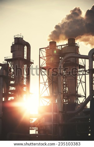 Retro filtered picture of smoky chimneys silhouettes against sun. Air pollution concept. - stock photo