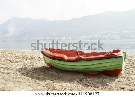 Retro fishing open deck motor boat is docked on Greek Telendos island sandy coastline - stock photo