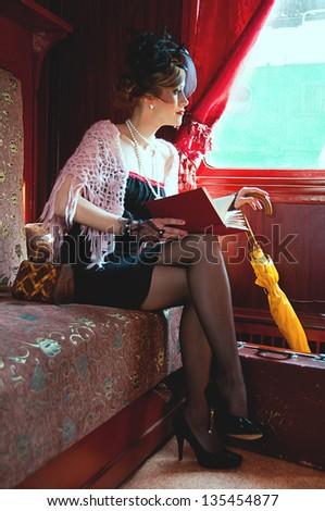 Retro girl reading book in  wagon train - stock photo