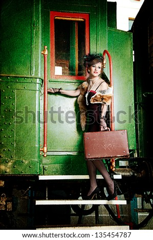 Retro girl with suitcase near the old train - stock photo