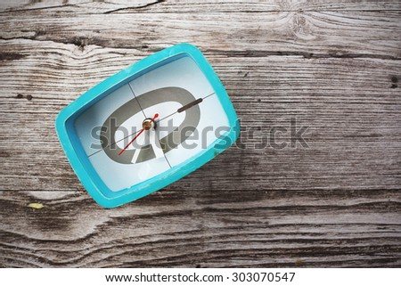 Retro green alarm clock on the wooden background. Toned image. Top view. - stock photo