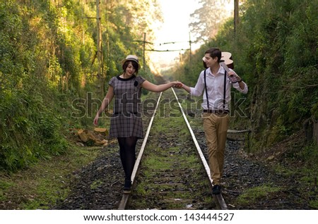 Retro hip hipster romantic love couple walking vintage train tracks - stock photo