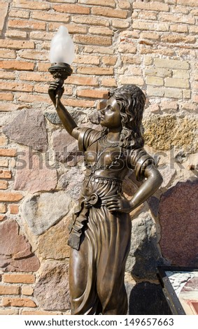 retro historic nympho sculpture near museum entrance holding lighting lamp in hand.  - stock photo