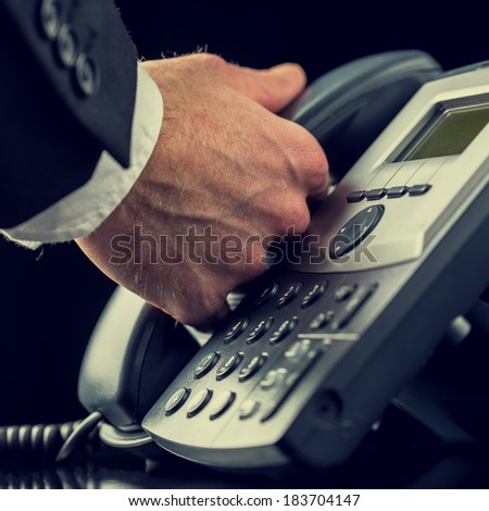 Retro image of a businessman making a call on a landline telephone lifting the handset off the cradle of the instrument, closeup of the hand and keypad. - stock photo