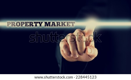 Retro image of a male hand activating a Property market button on virtual screen. - stock photo