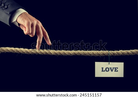 Retro image of a man walking his fingers along a length of rope or a tightrope towards Love. - stock photo