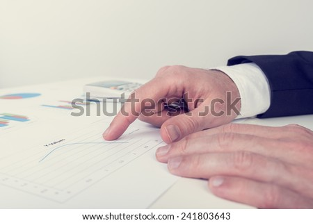 Retro image of businessman analysing printed business documents as he sits at his white desk pointing to one line chart, in a business analysis and strategy concept. - stock photo