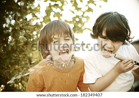 Retro image of cheerful kids drinking water from the pipe - stock photo