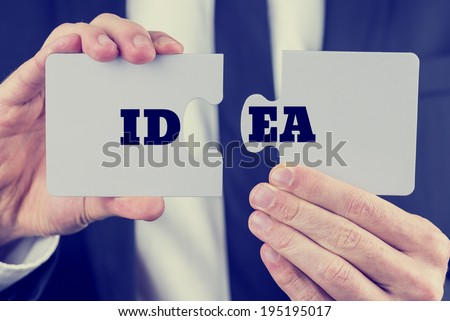 Retro image of male hand  holding word Idea  split over two puzzle pieces. Conceptual of innovation and creativity. - stock photo