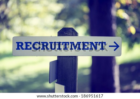 Retro image of recruitment signboard on a wooden post with a right pointing arrow. - stock photo