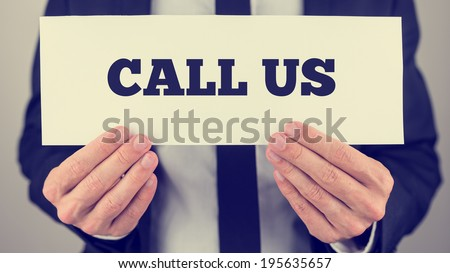 Retro instagram style image of a businessman holding card with Call us sign. - stock photo