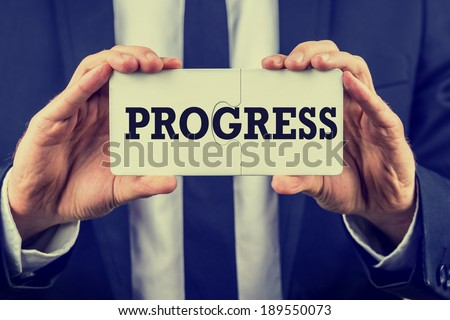 Retro instagram style image of a businessman holding two joined jigsaw puzzle pieces with the word - Progress - conceptual of having found a solution to a problem or overcome a challenge. - stock photo