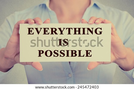 Retro instagram style image of businesswoman hands holding card with phrase message Everything is possible conceptual of optimism and determination isolated grey office wall background  - stock photo