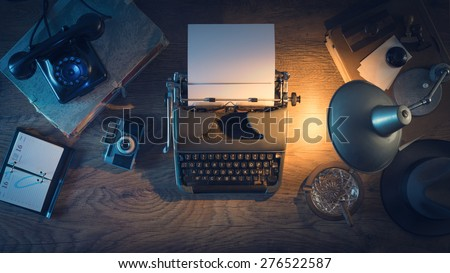 Retro journalist's desk 1950s style with vintage typewriter, phone and lamp at night time, top view - stock photo