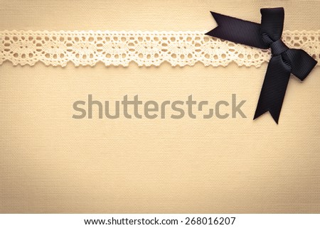 Retro lace and bow over real hand made paper background. - stock photo