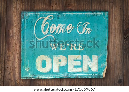 Retro light blue come in we're open sign on an old wooden background - stock photo