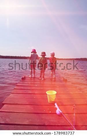 Retro look image of children on dock fishing - stock photo