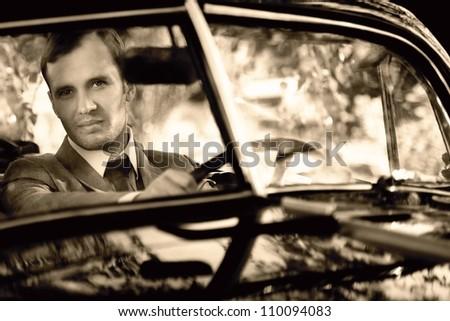 Retro man behind steering wheel - stock photo