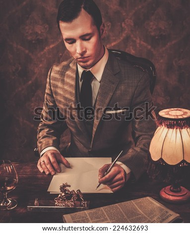Retro man in grey suit holding a pen - stock photo