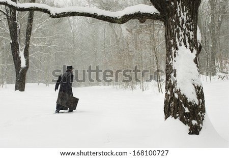 retro man with suitcase walking in snow - stock photo