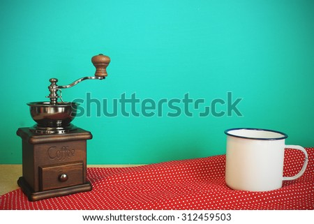 Retro manual coffee grinder and mug on tablecloth front mint green background. Vintage effect. - stock photo