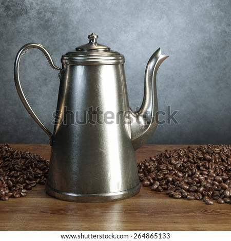 Retro metal coffee pot with pile of roasted coffee beans on wooden table behind grey wall background   - stock photo